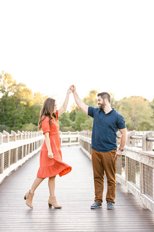 Cute couple dancing on bridge smiling Pickerel Lake Park Grand Rapids engagement session