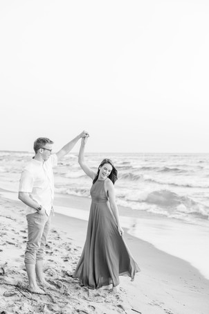 Engagement Photos Tunnel Park Beach Holland Michigan Engaged Couple twirling in long blue dress on the beach