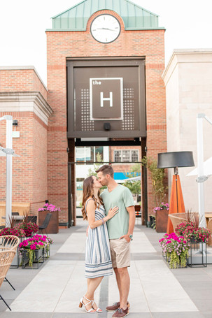 engaged couple standing kissing at the H clock tower downtown Midland Michigan