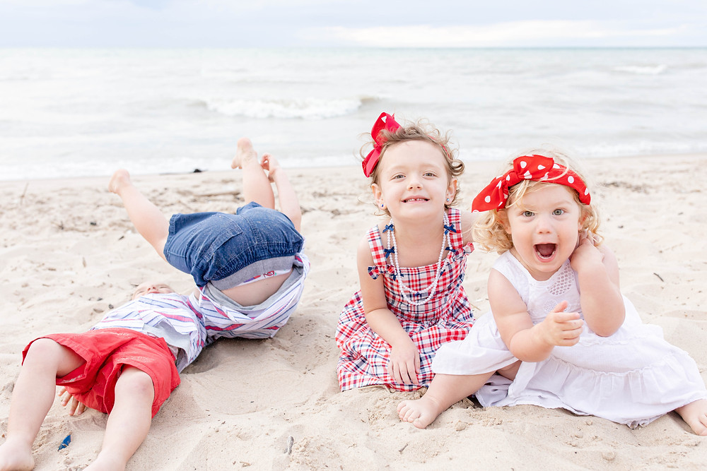 South Haven Family shoot small children cousins sitting and falling down on the beach at Lake Michigan red white and blue outfits