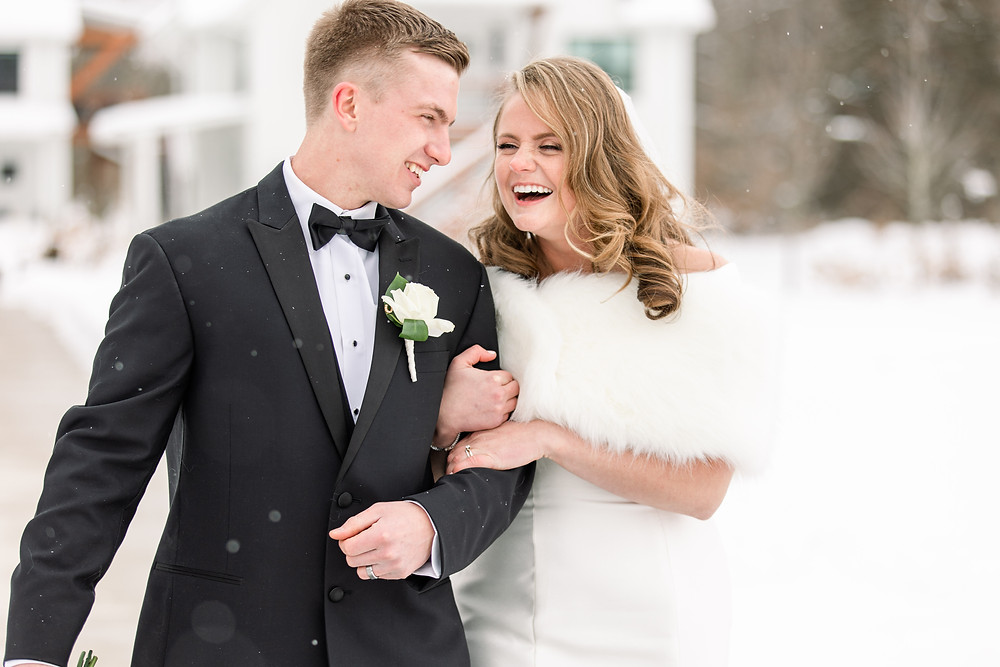 Josh and Andrea wedding photography husband and wife photographer team michigan venue Bay Pointe Woods shelbyville snow winter wedding bride and groom walking laughing smiling