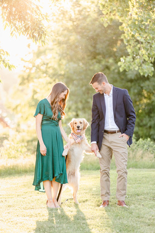 engaged cute couple holding up dog at trees near The Tridge Midland Michigan