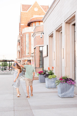 engaged couple walking and twirling downtown Midland Michigan