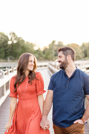 Cute couple smiling walking on bridge Pickerel Lake Park Grand Rapids engagement session