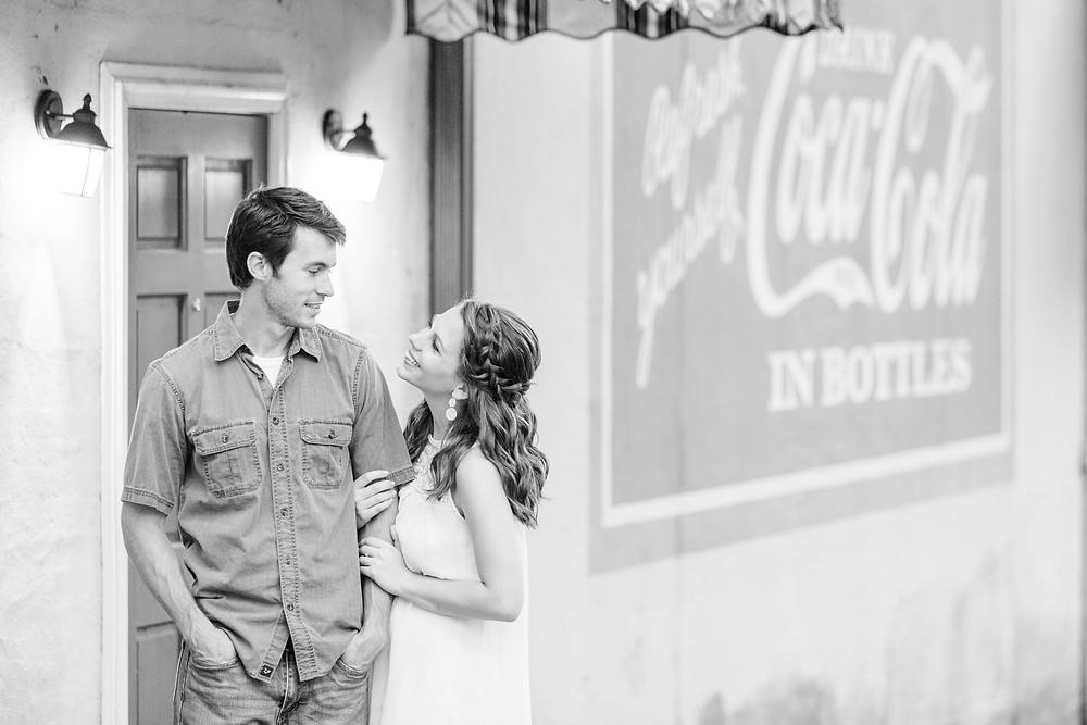 engagement photos cute couple downtown Milledgeville Georgia Coca Cola sign on building wall