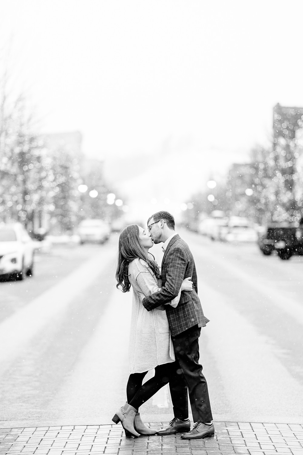 Josh and Andrea wedding photography husband and wife team michigan Grand Haven Rosy Mound engagement session fiance snowy town kissing street