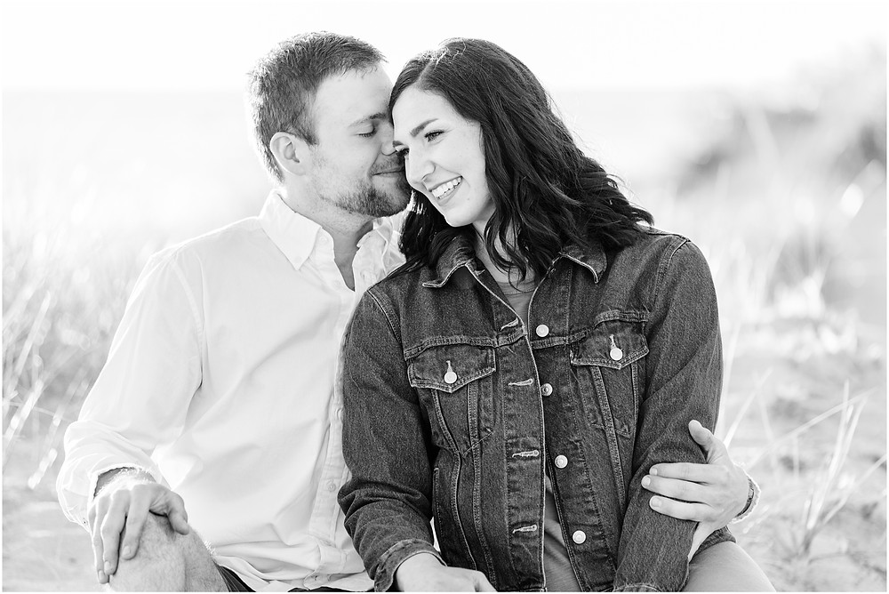 Josh and Andrea wedding photography husband and wife photographer team michigan pictures Lake Harbor Park engagement pictures session photo shoot fiance kissing sitting