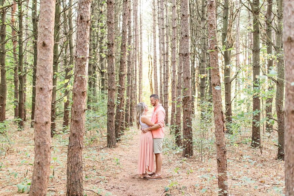 Engagement Photos Al Sabo Land Preserve Kalamazoo Michigan couple hugging in Tall row of Pines