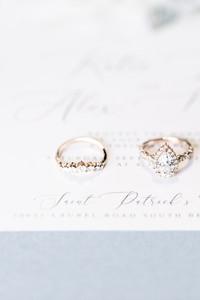 wedding band and engagement ring on invitation flat lay photo