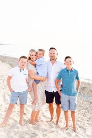 Family of 5 photos standing on beach sand Lake Michigan