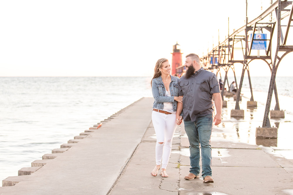 Engagement Photos Engaged Couple South Haven Beach Lighthouse Pier Michigan Engaged Couple walking on pier holding arm