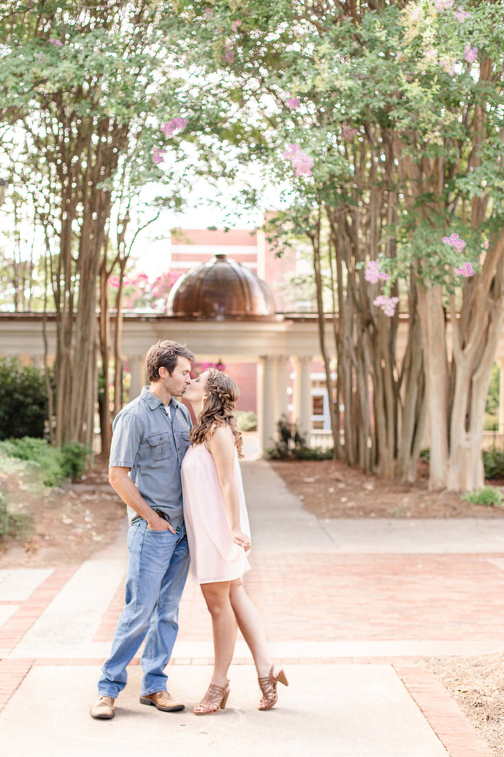 engagement photos cute couple kissing flowering trees Milledgeville GA Georgia College and State University