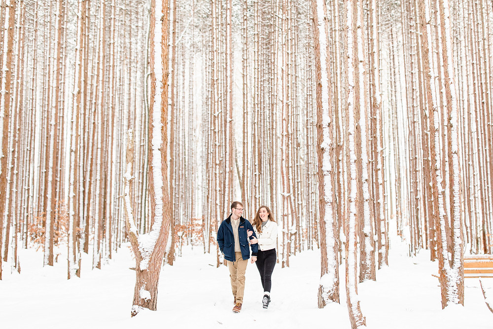Josh and Andrea wedding photography husband and wife team michigan Grand Haven Rosy Mound engagement session fiance snowy forest woods walking smiling
