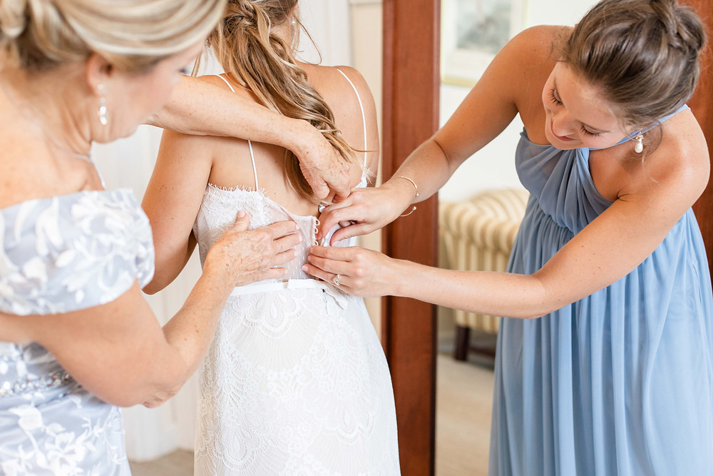 buttoning back of wedding dress mom and sister and bride Kent Country Club Wedding Grand Rapids