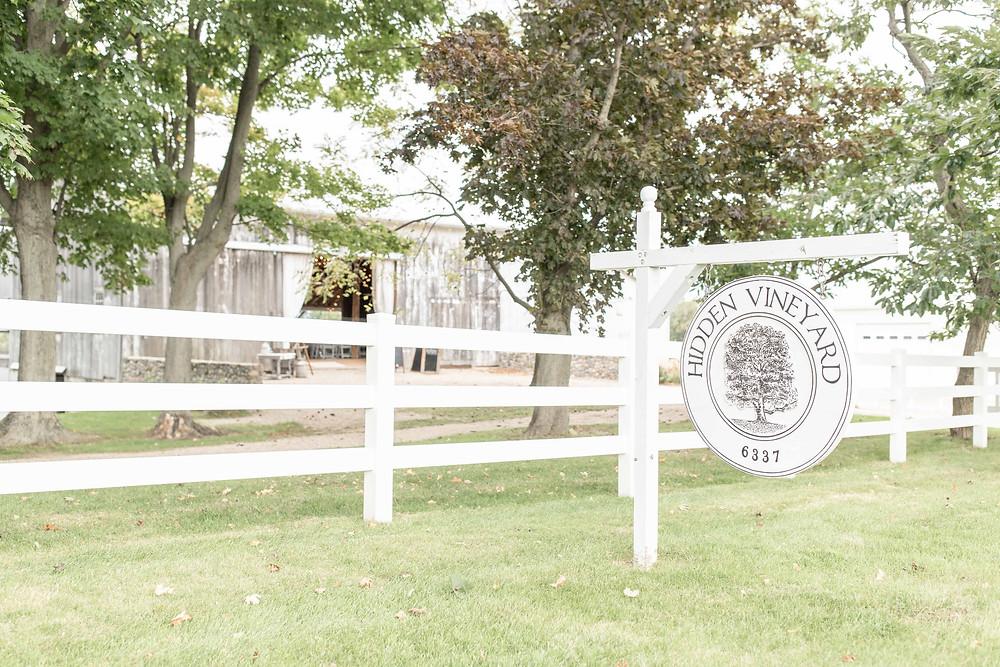 hidden vineyard wedding barn sign white fence