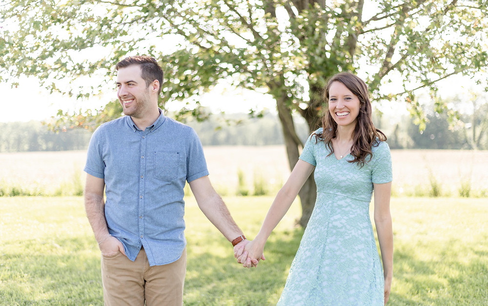 Photographer man and woman holding hands smiling and laughing