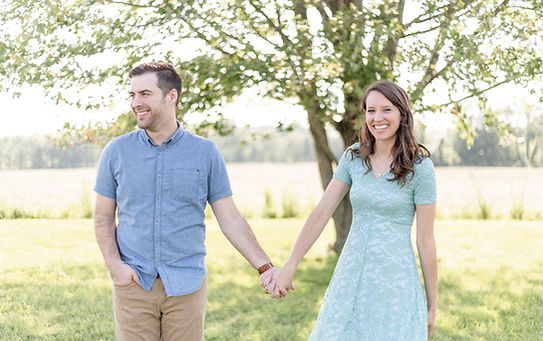 josh and andrea photography husband and wife team michigan man and woman standing in field smiling holding hands
