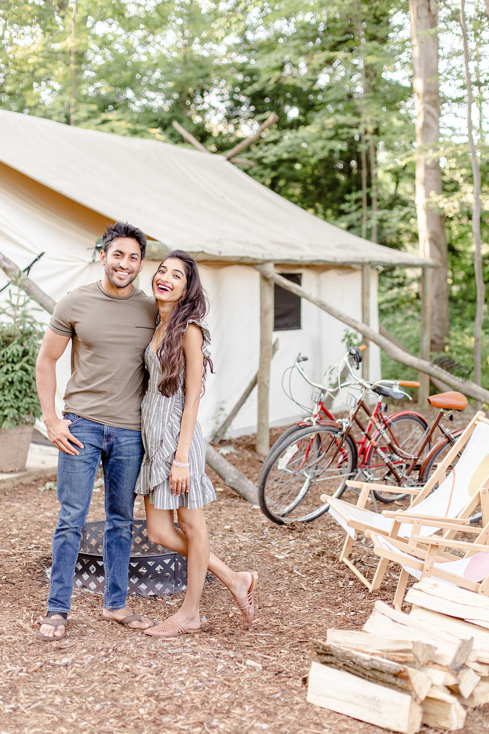 cute couple standing front of tent bikes lounge chairs fire pit laughing The Fields of Michigan South Haven luxury glamping experience