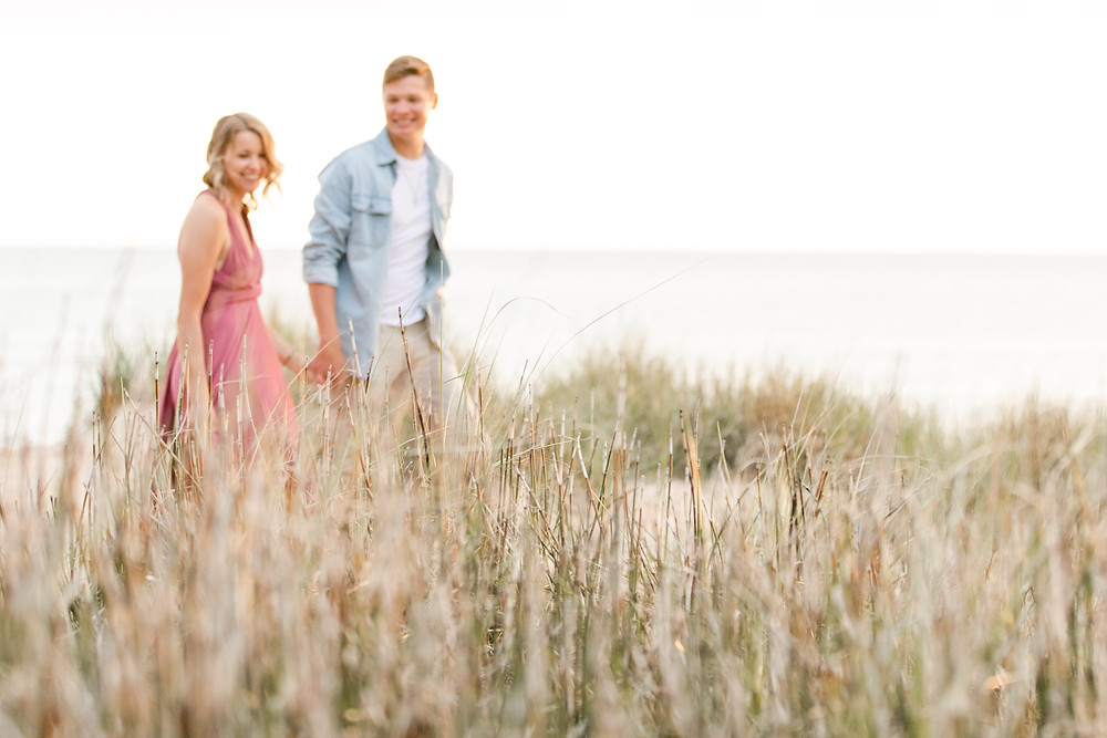 south haven man and women smiling beach engagement photos grass walking