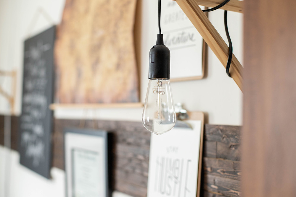 artistic lightbulb hanging near wood