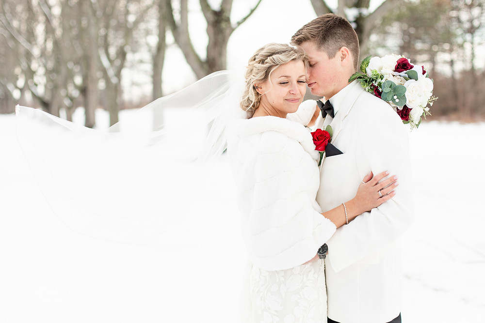 josh and Andrea photography husband and wife team michigan winter wedding south haven bride and groom smiling standing in snow forest