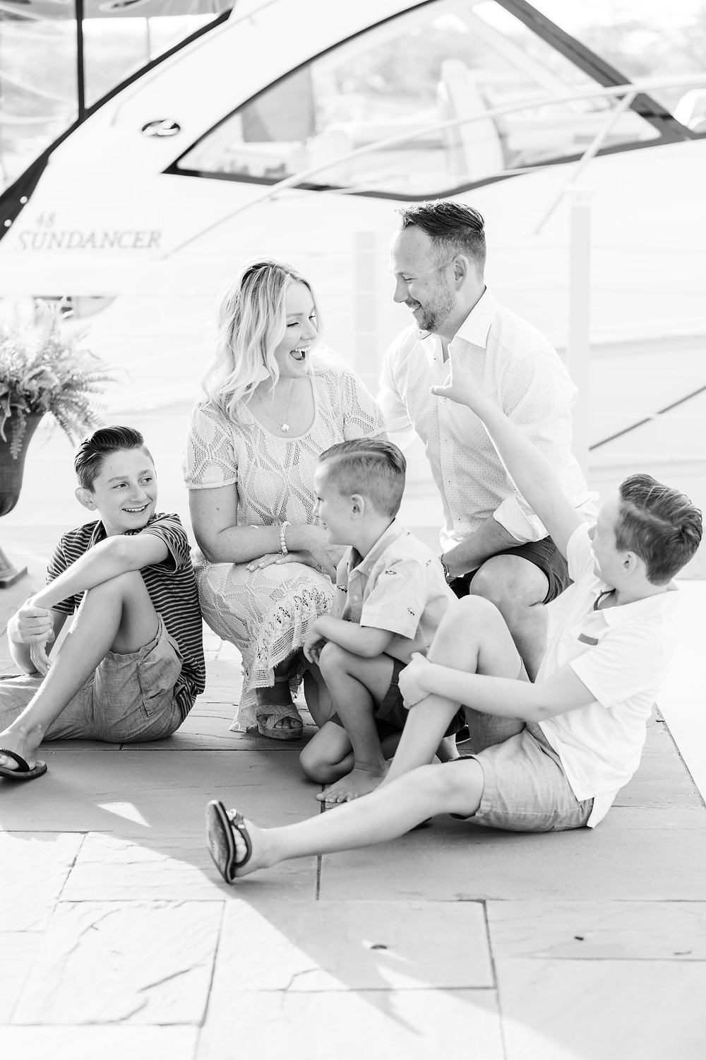family of 5 sitting and laughing by yacht boat new buffalo michigan