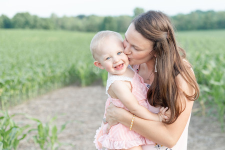 cute family photo shoot daughter smiling holding grass spring