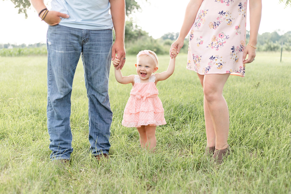 cute family photo shoot daughter smiling holding hands grass spring