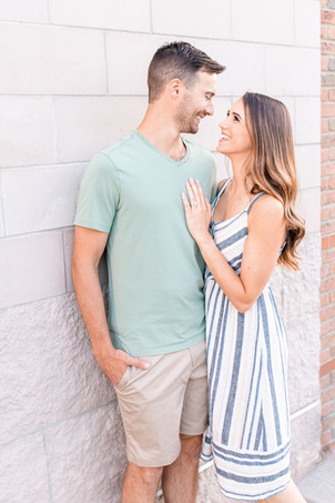 engaged couple standing against wall downtown Midland Michigan