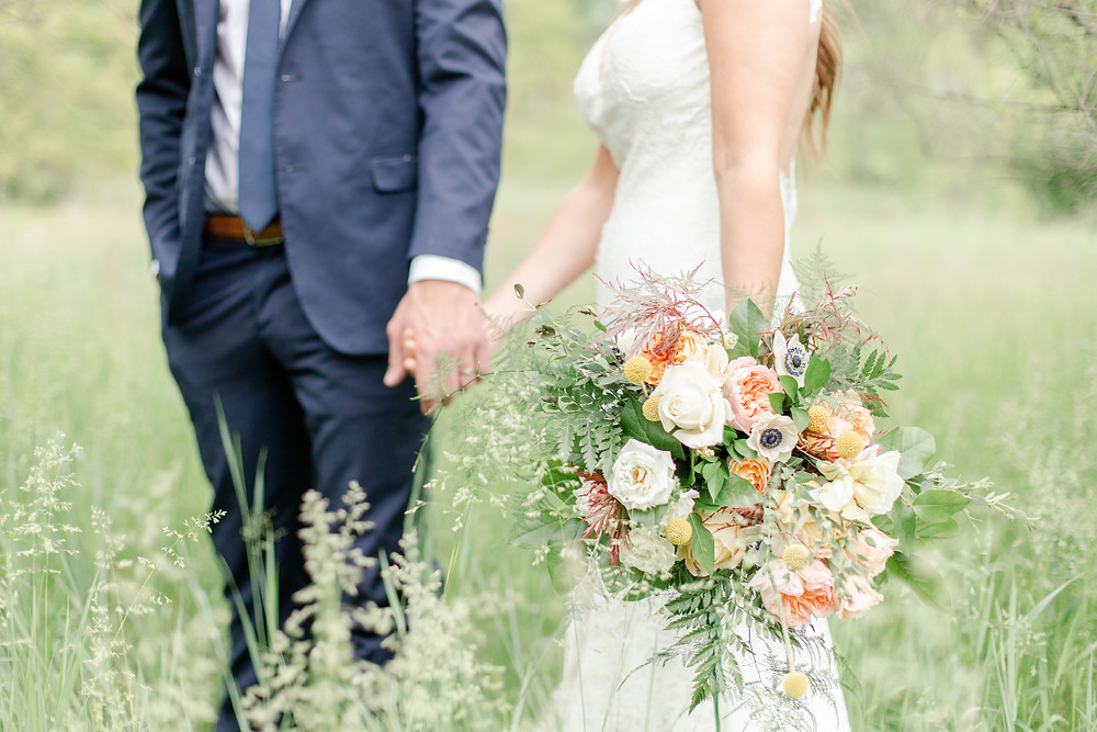 bouquet bride and groom walking in field in the details byron center truer design