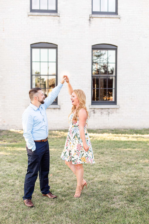 engagement photos cute couple twirling journeyman distillery weddings three oaks michigan