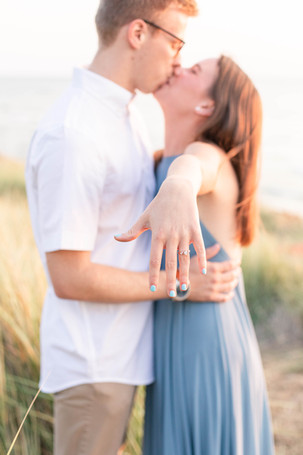 Engagement Photos Tunnel Park Beach Holland Michigan Engaged Couple kissing and holding out engagement ring hand