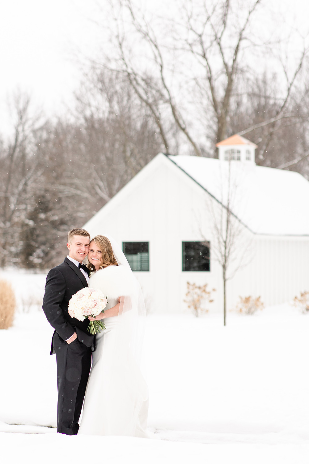 Josh and Andrea wedding photography husband and wife photographer team michigan venue Bay Pointe Woods shelbyville snow winter wedding bride and groom smiling