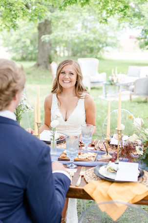 bride and groom sitting at table reception in the details byron center truer design