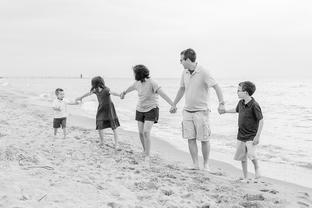 family holding hands walking on the beach Lake Michigan beach South Haven Michigan