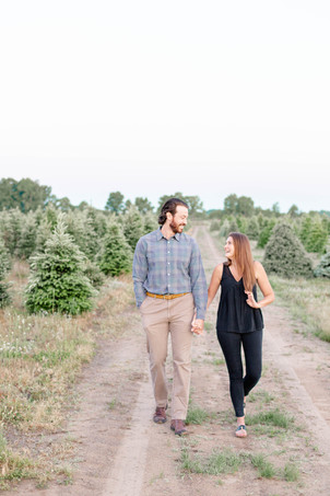 cute couple walking together engagement shoot Christmas tree farm