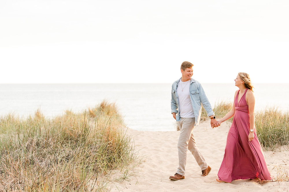 south haven man and women smiling beach engagement photos walking