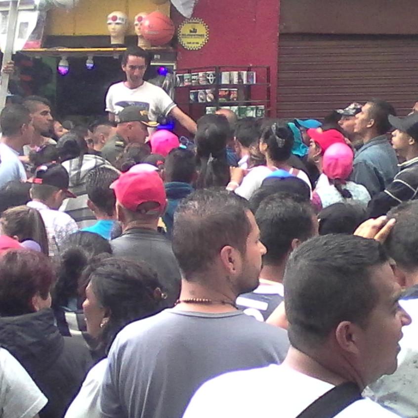 En la fotografía se puede observar a un Policía intentando explicar a decenas de vendedores informales, que tiene la orden de desalojarlos por las buenas o por las malas. / Foto: Róbinson Ospina Buitrago.