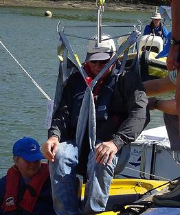 disabled sailor beig hoisted into a hansa dinghy at dart sailability