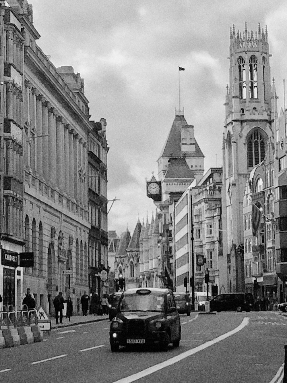 A black and white picture of fleet street: a back taxi  is on the road, and the royal courts of justice in the blackground