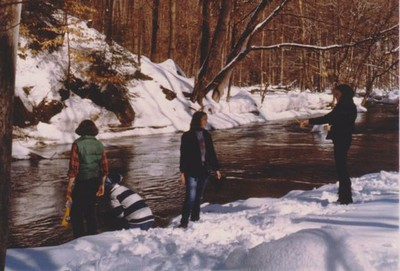 Campers by the creek in winter, 1980