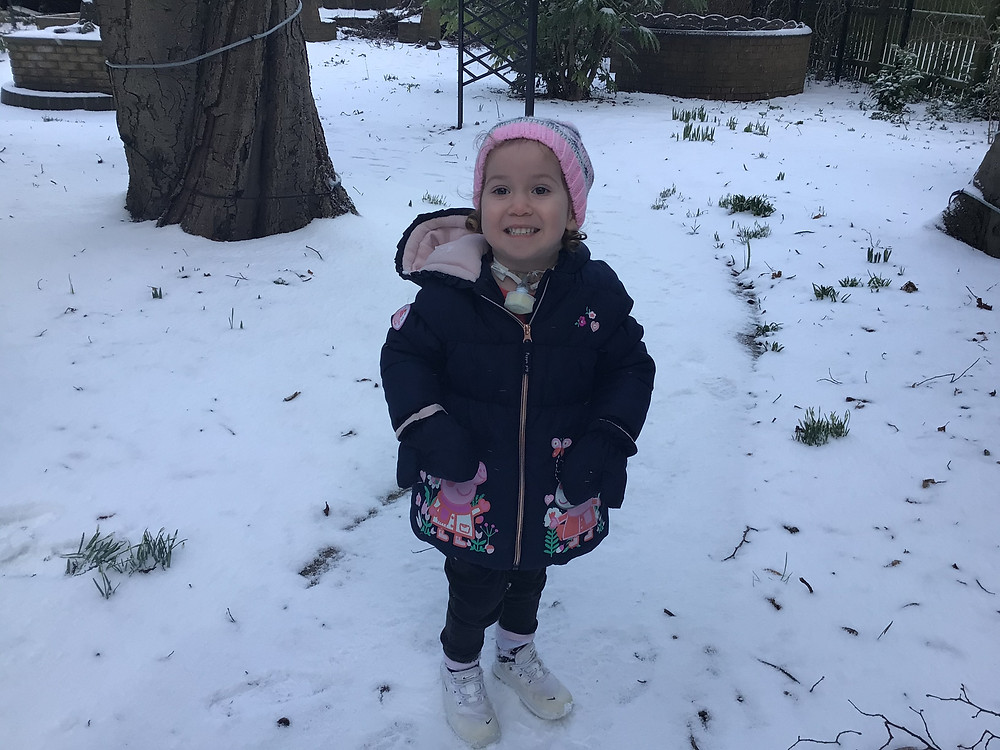 A young child smiling in the snow