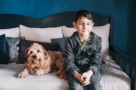 Ein Kind und ein brauner Hund sitzen gemeinsam auf einem Bett