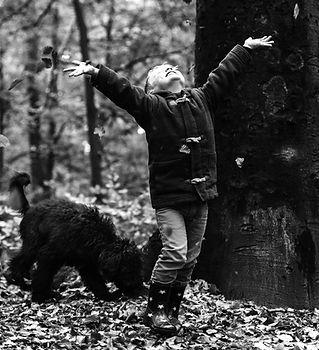 Schwarz-weiß Bild eines Kindes mit Hund im Laub