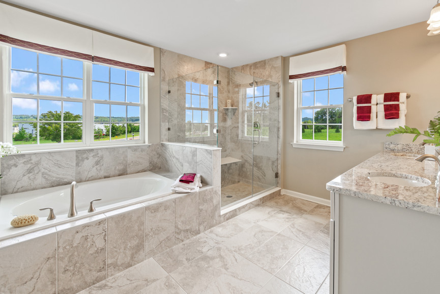 Marble bathroom with red accents and a large glass shower