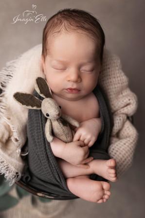 nouveau-né couché sur le dos avec doudou lapin