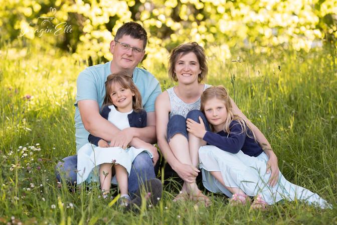 famille posée de face assise dans l'herbe