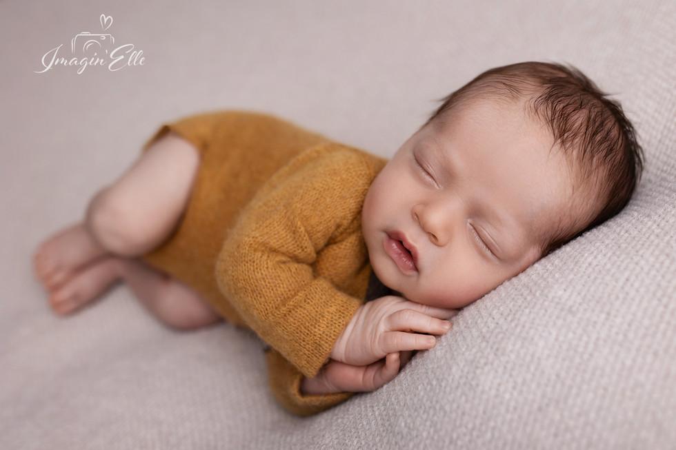 nouveau-né couché sur le côté vêtement moutarde