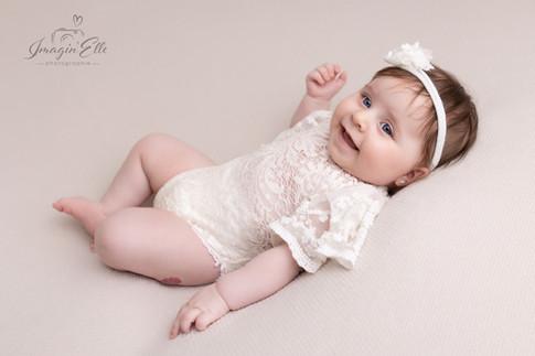 bébé sur le dos de profil habillé en dentelle blanche avec bandeau