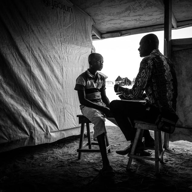 Artist Didier Kassai interviews young boy